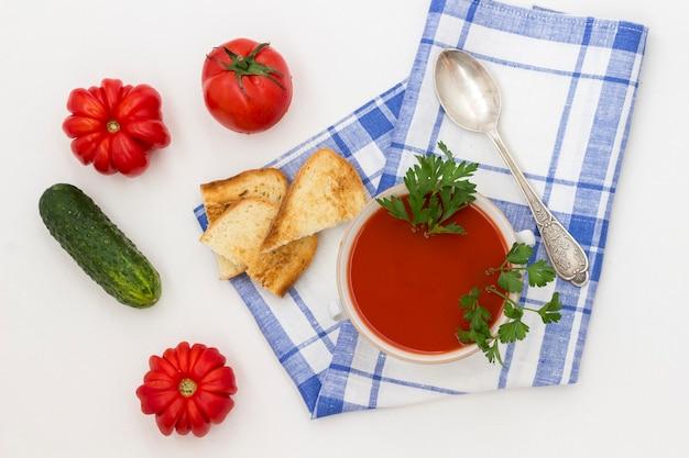 Koude zomerse tomatensoep. blauw geruit servet. set producten voor gazpacho. witte achtergrond
