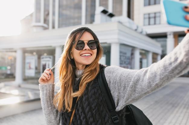 Koude zonnige dag in het centrum van stijlvolle vrolijke vrouw selfie portret maken op straat. reizen met rugzak, moderne zonnebril op, wollen trui, plezier maken, genieten van vrije tijd.