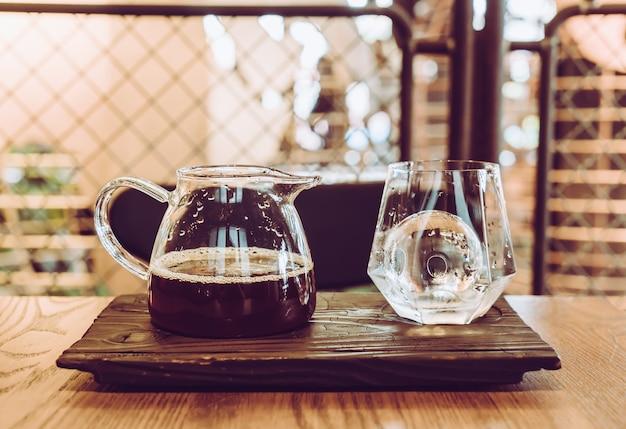 Koude zwarte koffiekruik met glas en ijs in coffeeshop