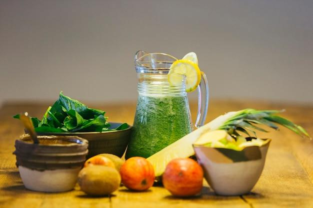 Koudgeperste spinazie-sap in een pot omringd door de gebruikte ingrediënten