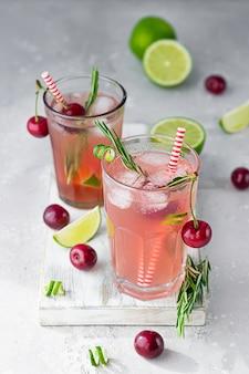 Koudroze alcoholvrije cocktail met kersen, limoen en rozemarijn op lichte houten snijplank.