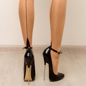 Kousen op mooie vrouwelijke benen met hoge hakken. - afbeelding