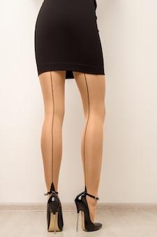 Kousen op mooie vrouwelijke benen met hoge hakken.