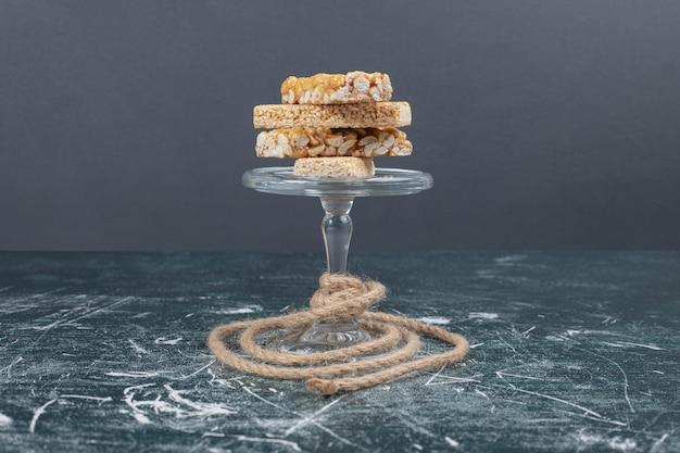 Kozinaki-snoepjes met zaden en noten op glasplaat met touw.