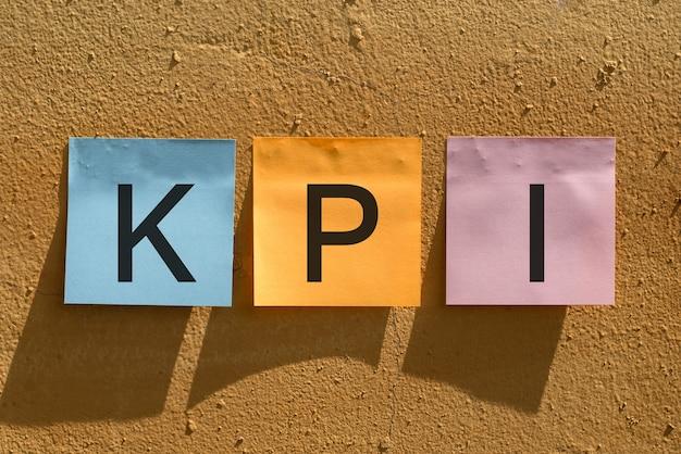 Kpi-tekst op blauw oranje en roze papier voor notities aan de muur. bedrijfsconcept