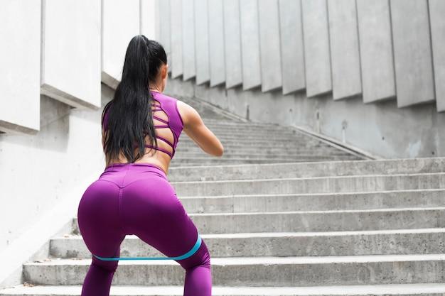 Kraakpanden. de band sportieve jonge vrouw die van de weerstand hurkende oefening doet