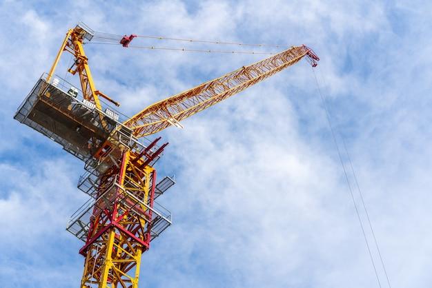 Kraan die in bouwwerf met wolk en blauwe hemel op achtergrond werkt.