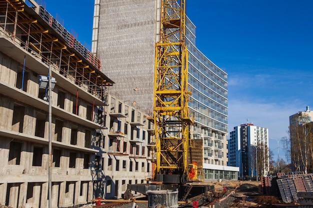 Kraan en bouwconstructieplaats tegen blauwe hemel