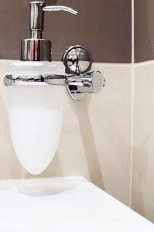 Kraan met zeepdispenser in badkamer.