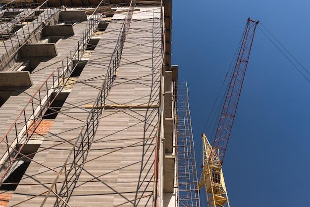 Kraan op de achtergrond van het gebouw in aanbouw