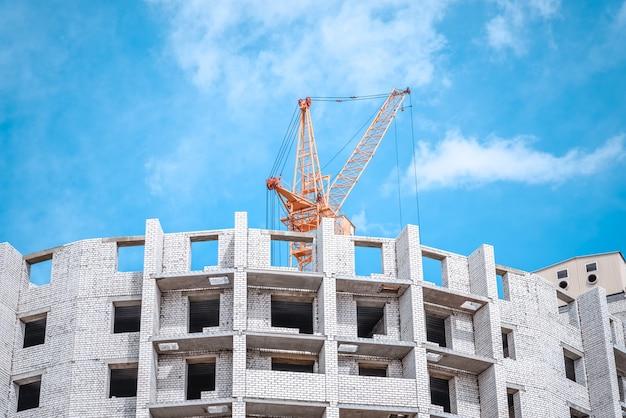 Kraan tegen hemel bouwen van een nieuw flatgebouw