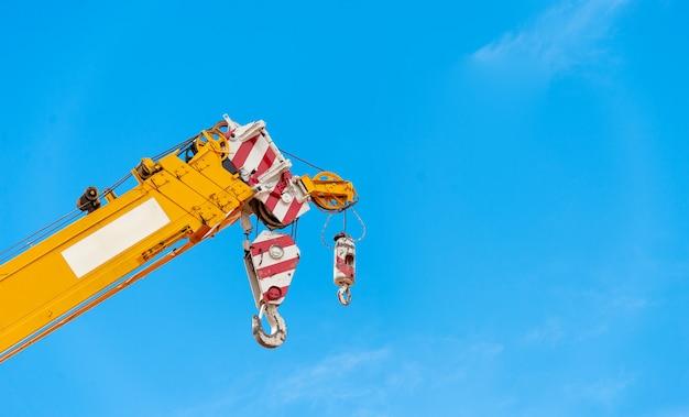 Kraan van de close-up de gele vrachtwagen in bouwwerf met zacht-nadruk en meer dan licht op de achtergrond