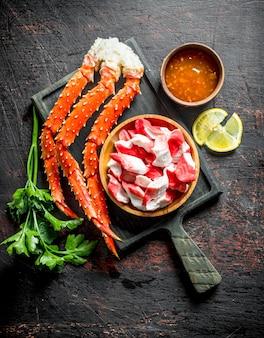 Krab en krabvlees op een bord met kruiden, saus en citroen. op donkere rustieke achtergrond