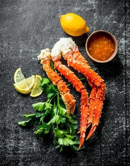 Krab met peterselie, schijfjes citroen en saus. op donkere rustieke tafel