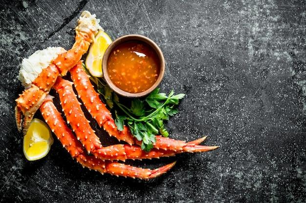 Krab met saus, kruiden en citroen. op donkere rustieke ondergrond