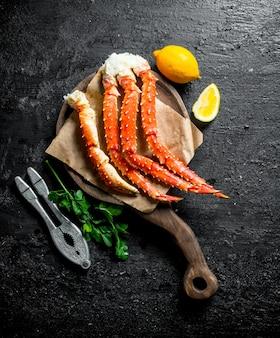 Krab op een snijplank met citroen en peterselie