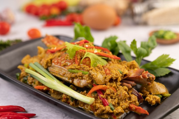 Krab roergebakken curry poeder op een zwarte plaat op de cementvloer.