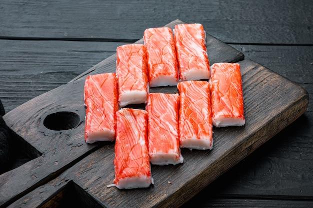 Krab stokken zeevruchten half afgewerkte vis gehakt met blauwe zwemmen krab set, op houten snijplank, op zwarte houten tafel achtergrond