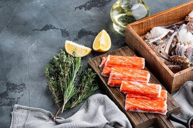 Krab stokken zeevruchten half afgewerkte vis gehakt met blauwe zwemmende krab set, op grijze achtergrond, met copyspace en ruimte voor tekst