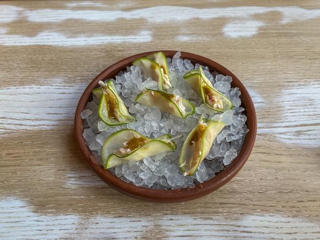 Krab taco met pittige mangosaus op een kussen van ijs in een keramische plaat op houten tafel. bovenaanzicht