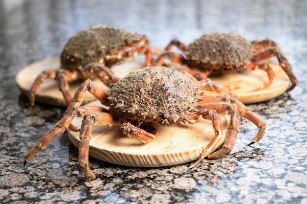 Krabben sluiten omhoog bovenop houten platen. zeevruchten op de voorgrond