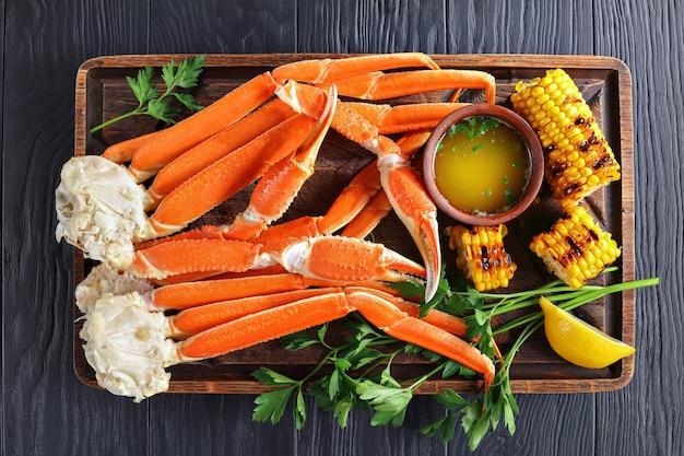 Krabbenpoten met gesmolten boter en gegrilde mais in kolven
