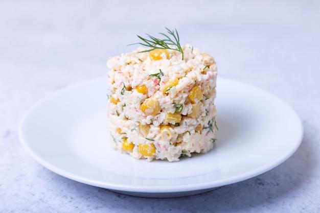 Krabsalade met maïs en eieren op een witte plaat. traditionele russische salade. detailopname.