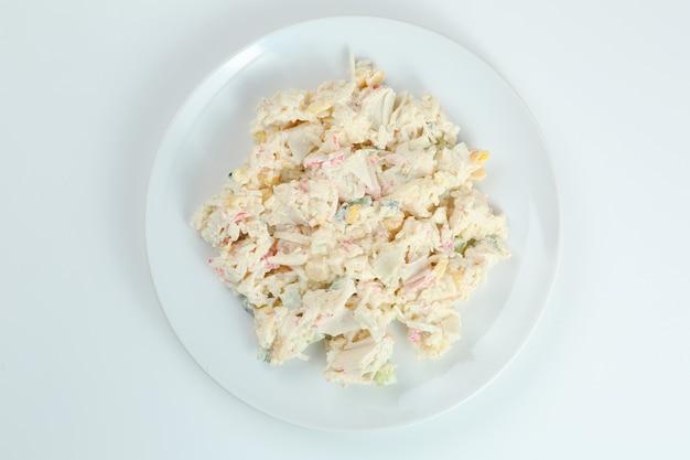 Krabsalade met rijst op witte plaatclose-up met exemplaarruimte. russische traditionele salade met krabstokken die op wit worden geïsoleerd