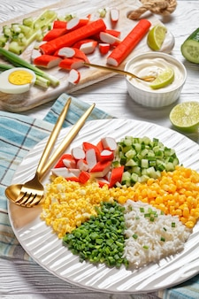 Krabsalade van surimi-sticks met ingeblikte maïs, komkommers, hardgekookte eieren van lente-ui, jasmijnrijst verdeeld in sectoren op een witte plaat op een witte houten achtergrond, bovenaanzicht, close-up