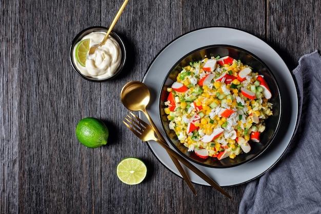 Krabsalade van surimisticks met groenten: maïs, komkommers, lente-ui, eieren, jasmijnrijst met limoen en mayonaisedressing geserveerd in een zwarte kom op een donkere houten ondergrond, bovenaanzicht, close-up