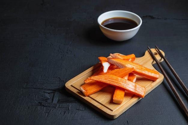 Krabstokken en japanse saus op een zwarte