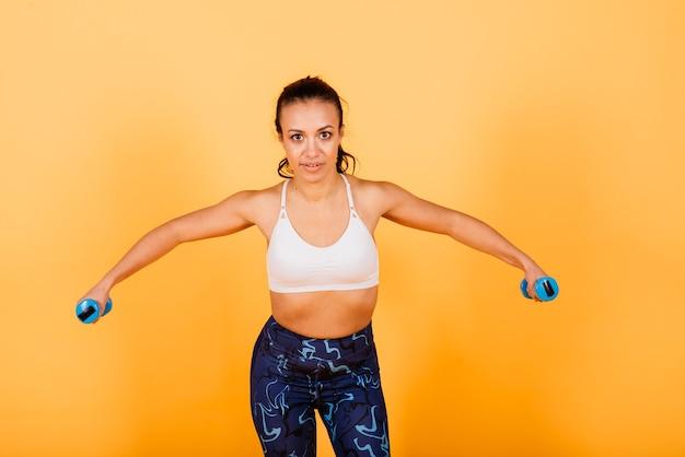 Kracht en motivatie. volledige lengte van jonge en slanke afrikaanse vrouw in sportkleding die in studio uitoefenen tegen gele achtergrond