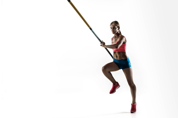 Kracht en schoonheid en zuiverheid. professionele vrouwelijke polsstokhoogspringer opleiding op witte muur. fit en slank vrouwelijk model oefenen. begrip sporten,
