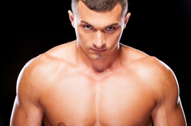 Kracht in hem. portret van een serieuze jonge shirtloze man die naar de camera kijkt terwijl hij tegen een zwarte achtergrond staat