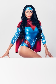 Krachtig en verleidelijk. mooie jonge vrouw in superheld kostuum camera kijken