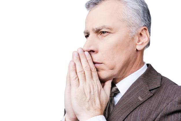 Krachtig gebed. zijaanzicht van een geconcentreerde volwassen man in formalwear die handen vasthoudt in de buurt van het gezicht en wegkijkt terwijl hij tegen een witte achtergrond staat