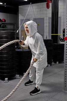 Krachtige arabische vrouw crossfit-trainer in hijab strijd training met touwen alleen in de sportschool, geconcentreerd op oefeningen met sportieve apparatuur