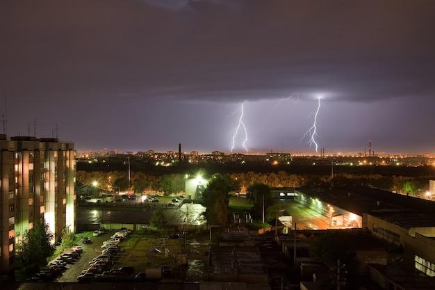 Krachtige bliksemflits verlicht de nachtelijke hemel en de stad
