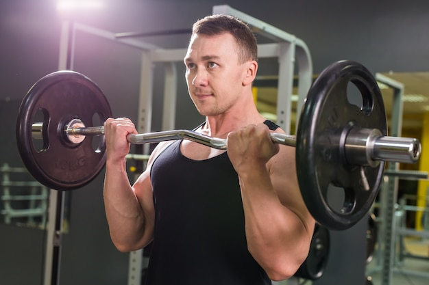 Krachtige bodybuilder die de oefeningen met barbell doet. foto van sterke man met naakte torso op donkere muur. kracht en motivatie.