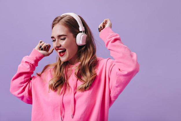 Krachtige dame in roze hoodie die naar muziek luistert in een koptelefoon en danst op de paarse muur