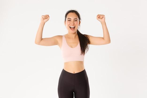 Krachtige en sterke aziatische vrouwelijke atleet, fitness meisje moedigt zichzelf aan voor een goede training, vuistpomp en schreeuwend vrolijk, witte achtergrond.