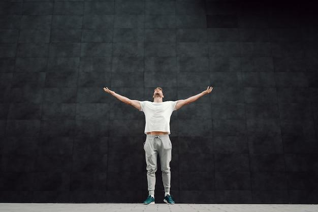 Krachtige kaukasische knappe fit bebaarde blonde sportman in trainingspak en in t-shirt hand in hand in de lucht en opzoeken terwijl je voor een donkere muur staat.
