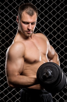 Krachtige kerel met domoren die spieren op omheining tonen