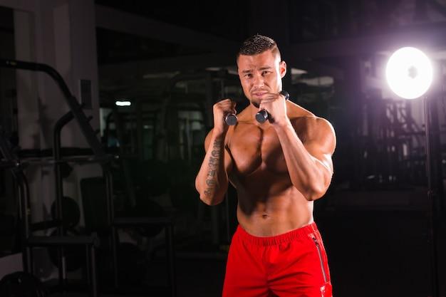 Krachtige man die boksoefeningen doet, direct geraakt met halters.