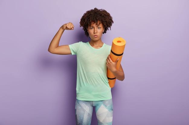 Krachtige sterke vrouw heft arm op, toont biceps, houdt fitnessmat vast voor gymtraining, gekleed in actieve kleding