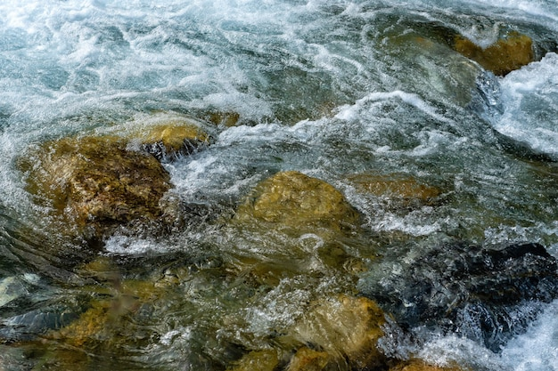 Krachtige stroom van water over de stenen, berg rivier close-up.