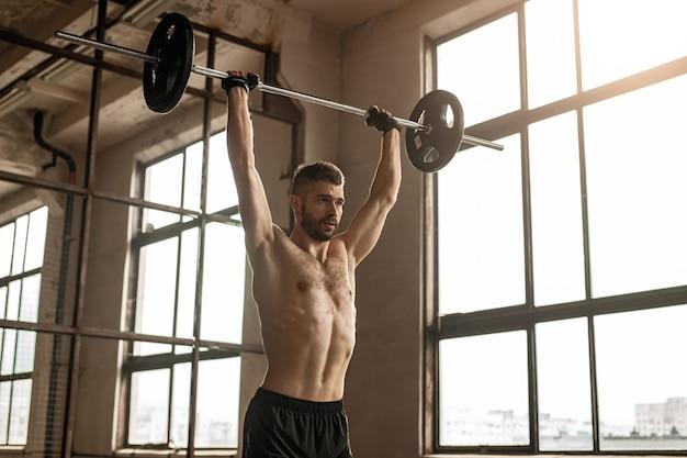 Krachtige volwassen bebaarde man met naakte torso overhead pers oefening met barbell doen tijdens intensieve gewichtheffen training in de sportschool