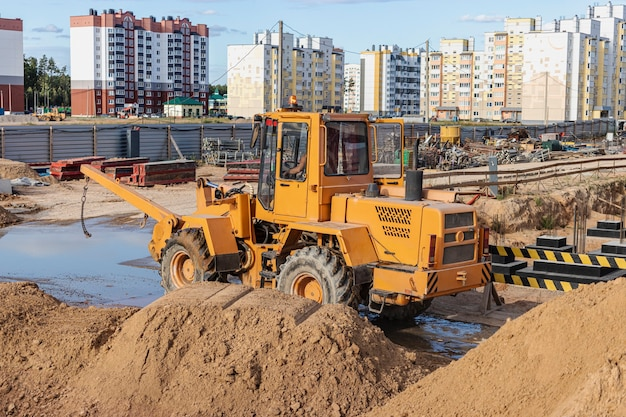 Krachtige wiellader voor het vervoeren van volumineuze goederen op de bouwplaats van een moderne woonwijk. bouwmachines voor het hijsen en verplaatsen van lasten.