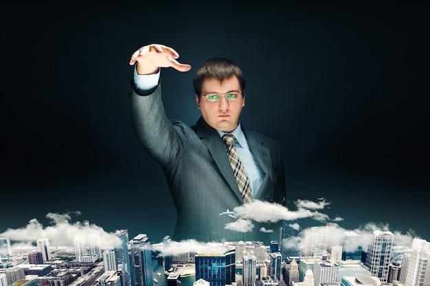 Krachtige zakenman in pak houdt zijn hand over het model van de stad, zwarte achtergrond. invloedrijke zakenman maakt plannen voor de toekomst