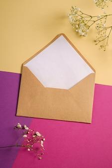 Kraft bruine papieren envelop met witte lege kaart en gypsophila bloemen